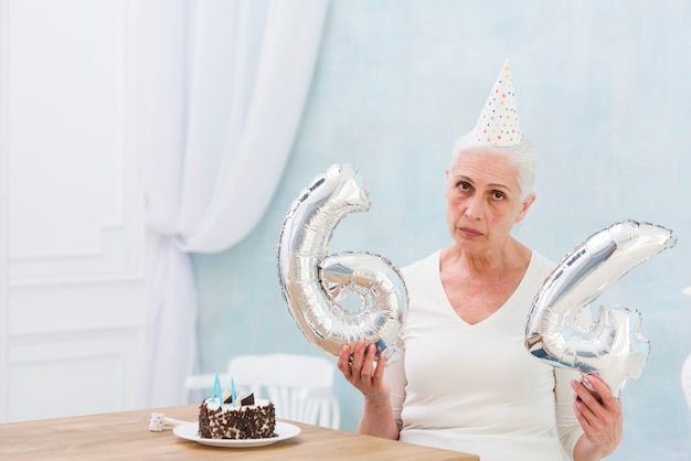 Sad woman holding foil balloon with cake on wooden table