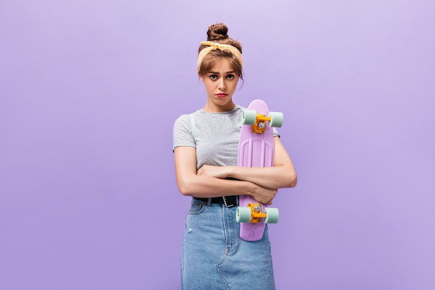슬픈 여자는 보라색 바탕에 longboard를 보유하고있다. 회색 셔츠와 데님 스커트 포즈에 노란색 머리띠와 실망 된 소녀.