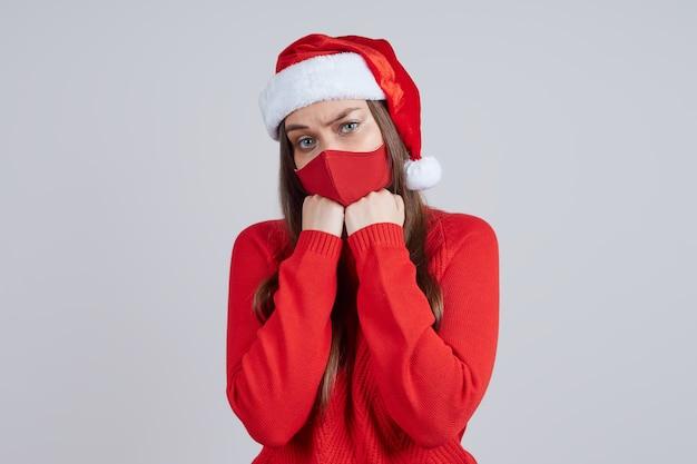 산타 모자에 보호 마스크에 슬픈 여자