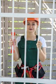 閉じた門の後ろに立っているつなぎの女の悲しい女性。彼女は疲れていて、ヘルメットとツールベルトを着用しています