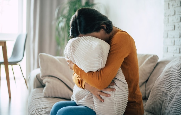Грустная женщина в глубокой депрессии сидит на диване, плачет и думает о плохом