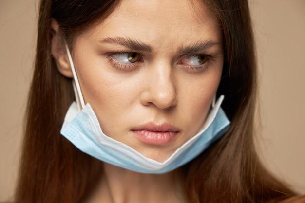 Грустная женщина в медицинской маске смотрит в сторону крупным планом портрет