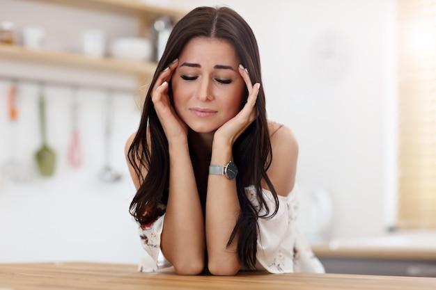 モダンなキッチンで悲しい女性