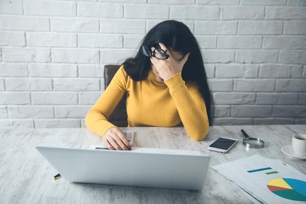 Грустная женщина на фоне офисного стола