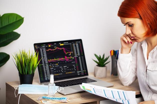 悲しい女性は流行のcovid-19の間に下落株価チャートを見ています