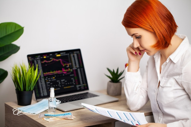 Sad woman is looking at falling stock charts during an epidemic covid-19