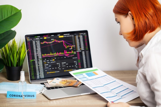 Sad woman is looking at falling stock charts during an epidemic covid-19.