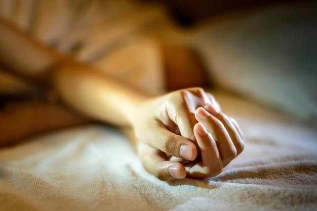 Sad woman is lying in bed at night , dark feeling