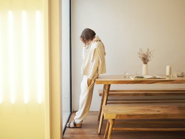 Грустная женщина стоит у окна