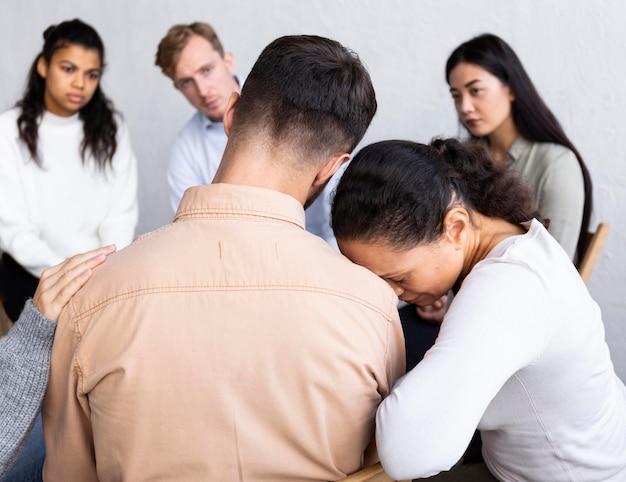 集団療法のセッションで男の肩に頭をもたれている悲しい女性