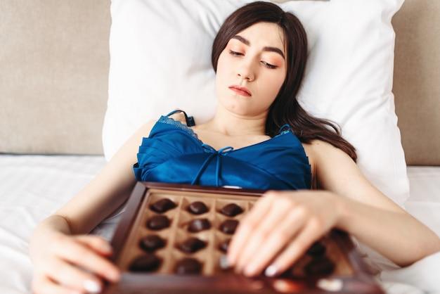 悲しい女性はベッドにあり、お菓子、女性のうつ病の概念を食べる。問題があると強調した女の子