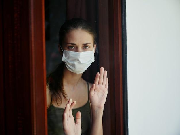 医療マスク検疫ロックダウンを身に着けている窓の外を見ている悲しい女性