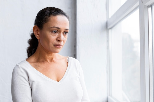 Sad woman looking through the window at a group therapy session