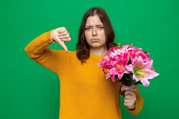 Sad woman showing thumb down and holding bouquet