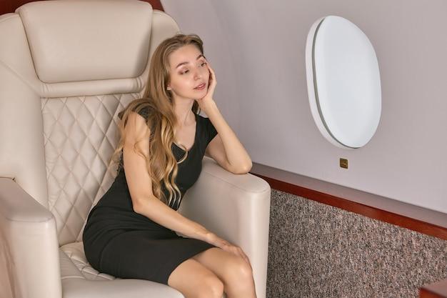 슬픈 여자는 개인 제트기 탑승 창 근처의 조수석에 앉아있다.