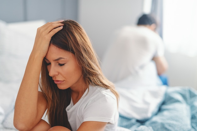 Sad woman sitting on the bed in bedroom in the morning and holding head after fight with husband.