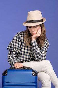 Sad woman sitting on blue luggage