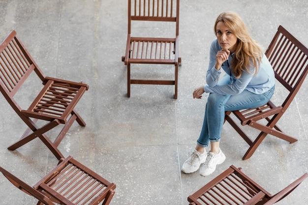 Donna triste che si siede sul colpo pieno della sedia