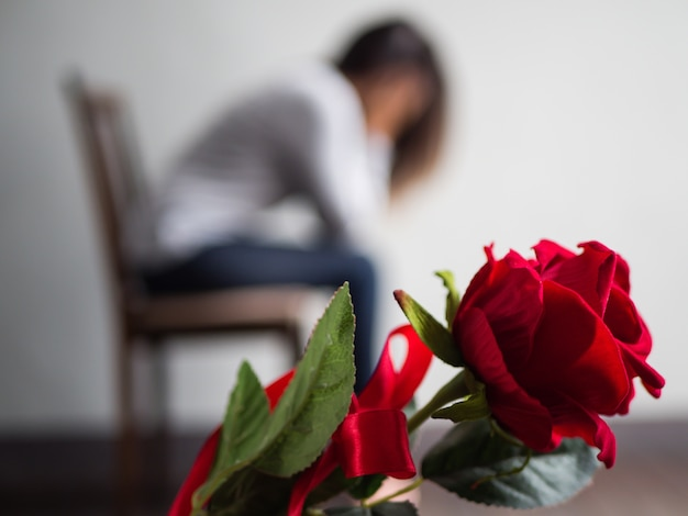 Sad woman sitting and crying with red rose in focus.