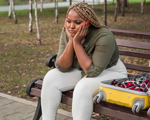 Triste donna seduta accanto al suo bagaglio aperto