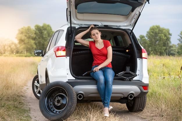 田舎道で壊れた車の開いたトランクに座っている悲しい女性