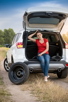 道路上の壊れた車の開いたトランクに座っている悲しい女性