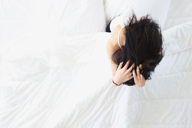 하얀 침대에 앉아 머리를 들고 있는 슬픈 여자 불면증 치료 개념
