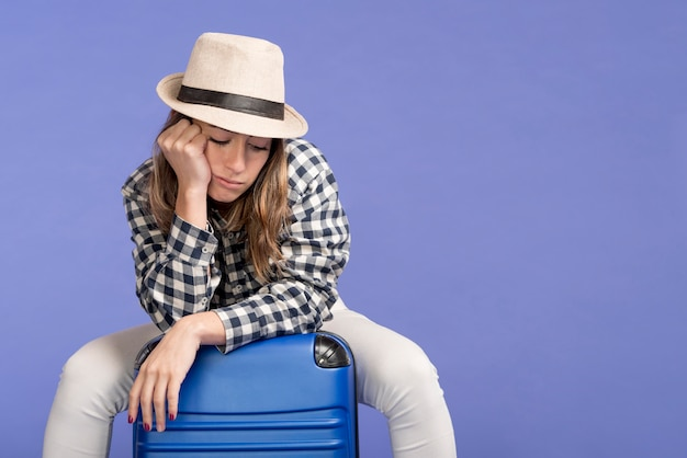Sad woman sitting on luggage