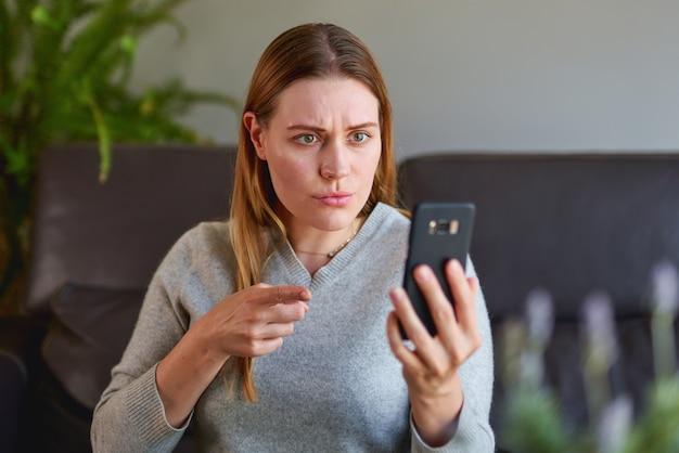 ノートパソコンでソファに座って、自宅で電話で話している悲しい女性。ノートパソコンと電話を使用して勉強している大学生。