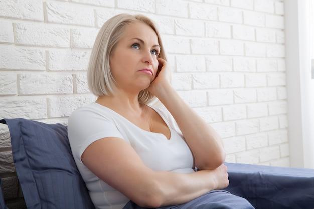 아침에 침대에 앉아 슬픈 여자. 우울한 폐경.