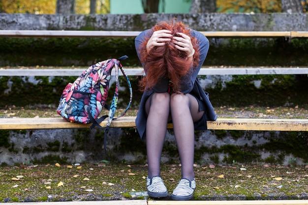공원에서 벤치에 앉아 슬픈 여자 프리미엄 사진