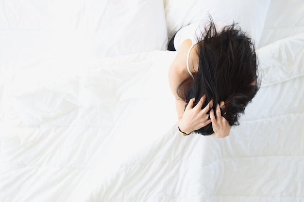 Sad woman sitting in white bed and holding her head top view insomnia treatment concept