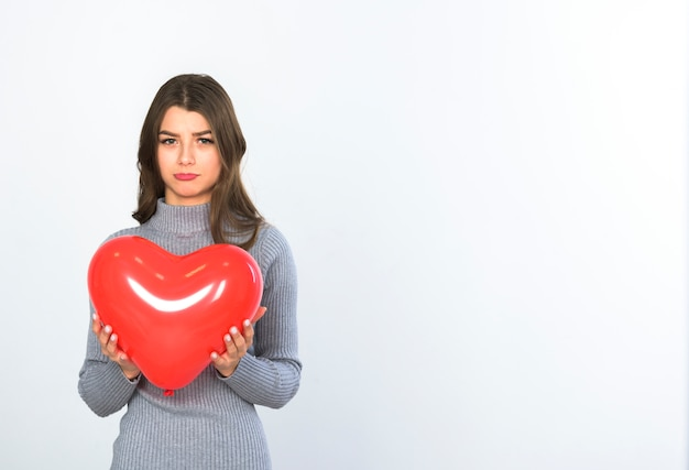 Sad woman standing with heart balloon