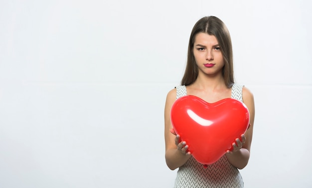 Sad woman standing with red heart balloon
