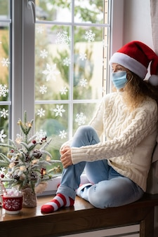 Sad woman stay at home in christmas time. winter holiday during pandemic coronavirus covid 19 concept