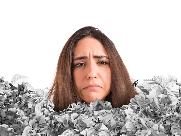 Грустная женщина в ловушке груды документов
