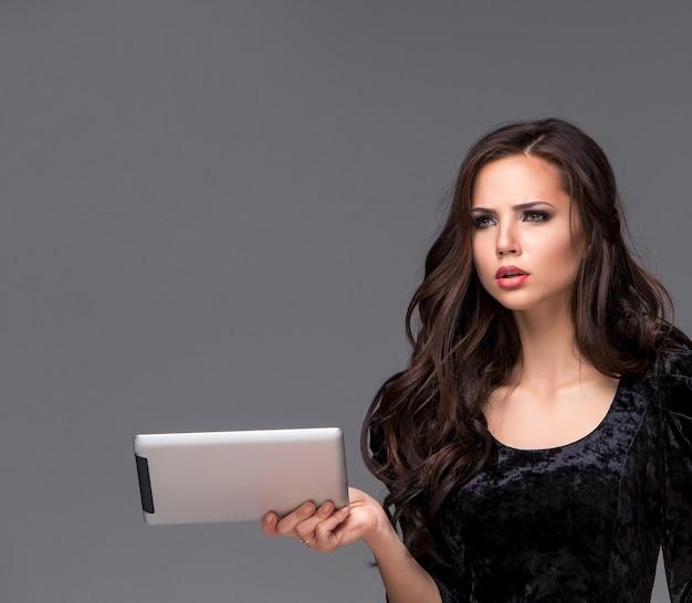 회색 배경에 태블릿을 사용하는 슬픈 여자