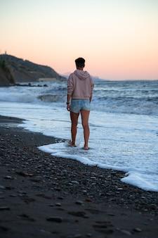Грустная женщина идет по пляжу с драматическими холодными волнами