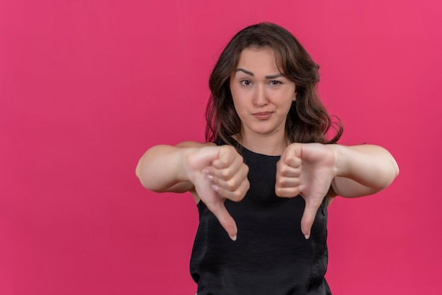 Sad woman wearing black undershirt her thumb to down on pink wall