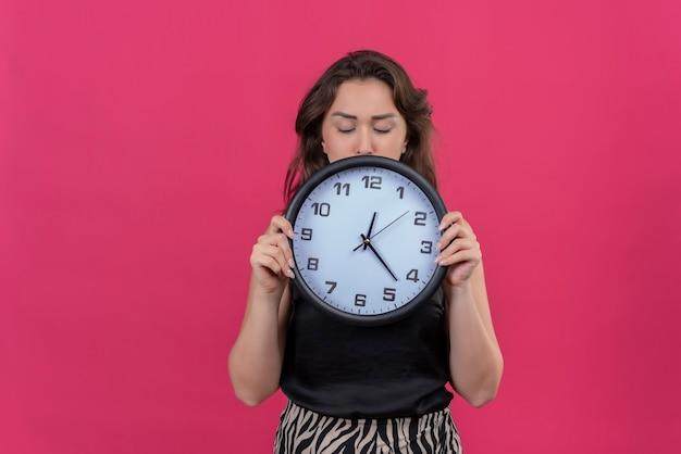 Sad woman wearing black undershirt holding wall clock on pink wall