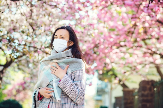 Грустная женщина в маске для лица во время карантина на улице