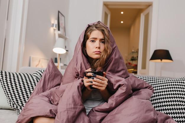 추운 아침에 뜨거운 커피를 마시는 아름다운 눈을 가진 슬픈 여자