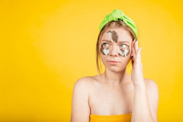 Унылая женщина с повязкой на глазу. портрет недовольной расстроенной дамы использовать пятна под глазами смотреть изолированно желтый цвет стены