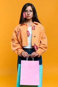 Donna triste con gli occhiali che tengono le borse della spesa e indossa una giacca con etichette di vendita