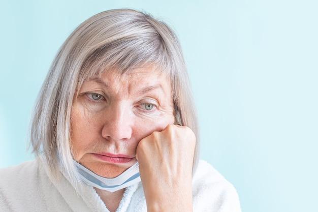 医療マスクを持つ悲しい女性。悲しいことに目をそらします。不安の概念、コロナウイルスの流行、19のパンデミック、老齢と病気、年金受給者、成熟した人々、ヘルスケア