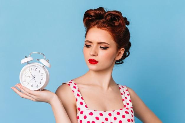 時計を見てピンナップヘアスタイルの悲しい女性。青い空間でポーズをとる水玉模様のドレスを着た魅力的な悲しい少女。