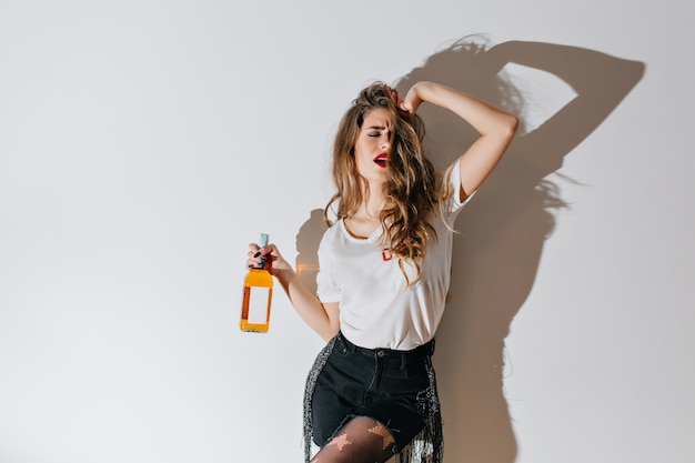 Donna triste con labbra rosse in posa con la bottiglia in mano