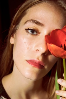 Sad woman with red tulip