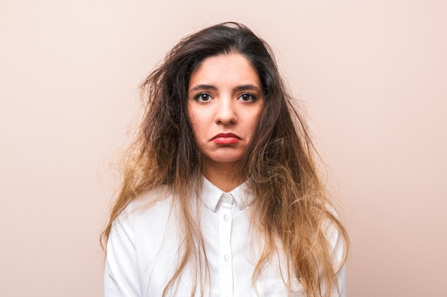 Sad woman with tangled hairs in white shirt against pink background. morning woman's routine