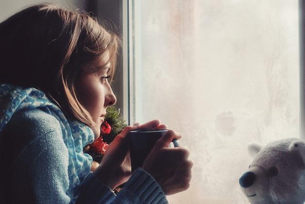 집에서 얼어붙은 창문 근처에서 꿈꾸는 스웨터를 입은 슬픈 여자